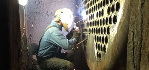 Welder working on a boiler